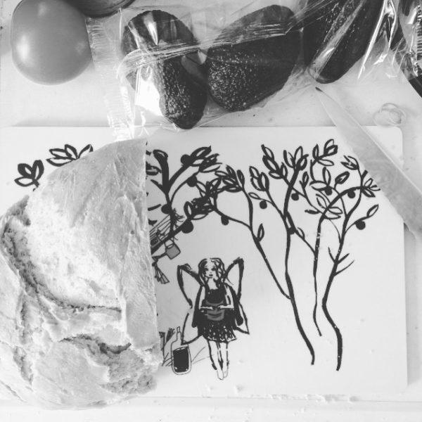 Svartvit bild på svensktillverkade skärbrädan, ett bröd ligger på den och avokado bredvid.