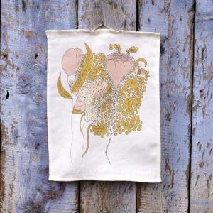 Vit kökshandduk med älva i rosa klänning vilandes på ett blad till en rosa ros