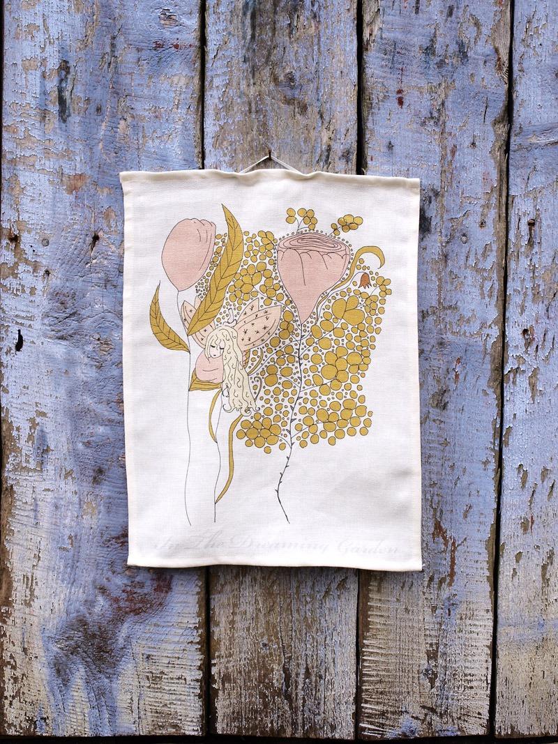 Lantlig kökshandduk i ekologiskt linne med sagomotiv i form av en rosa älva bland rosa blommor.