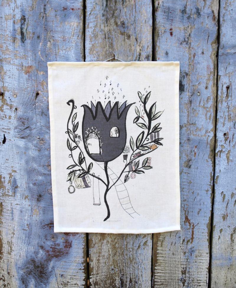 Kökshandduk i ekologiskt linne med ett sagomotiv i form av en stor blå blomma med dörr och repstege.