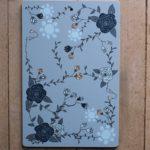 Blå skärbräda med mörblå rosor och ljusblå sommarblommor.