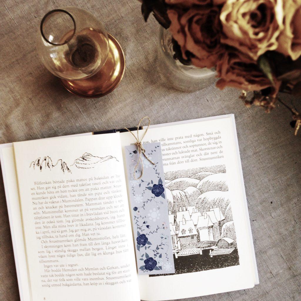 Bokmärke blå rosor i boken Sent i november, med fotogenlykta och torkade rosor bredvid.
