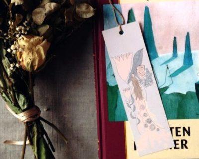 Bokmärket ligger i boken Kometen kommer av Tove Jansson, det är kaffe, en fotogenlampa och torkade blommor runt om