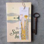 Gult bokmärke på aprikosa Sommarboken av Tove Jansson, med hav och en ö på framsidan, en nyckel ligger bredvid boken
