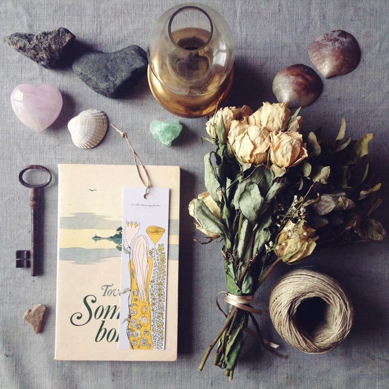 Gult bokmärke med flicka med långt hår, ligger på Sommarboken och runtom ligger hjärtstenar, torkade rosor och snöre