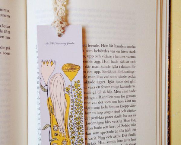 Bokmärke med flicka i gul klänning bland gula blommor