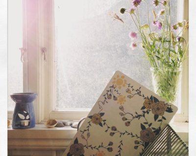 Vit skärbräda med rosa rosor och gula sommarblommor i lantkök