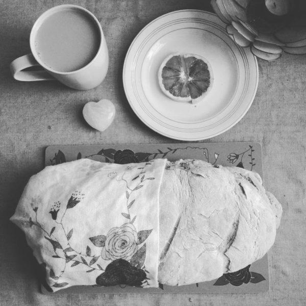 svartvit lantlig bild på blå rosor kökshandduk och hembakat bröd